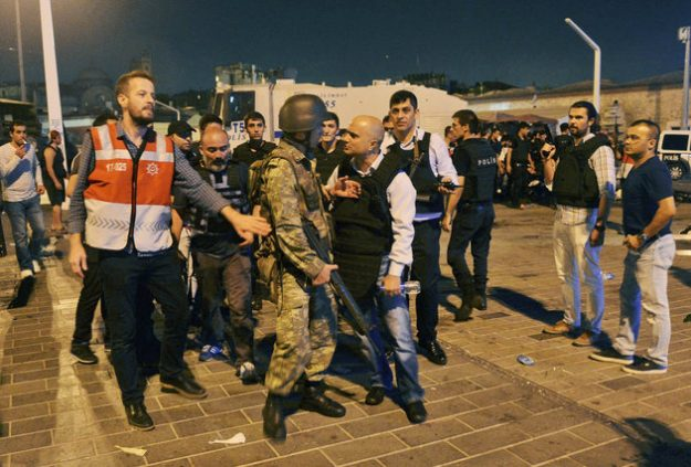 A Turkish police officer, center right, confronts a Turkish army officer, center left, that participated in the coup, after he was apprehended by civilians and handed over, in Istanbul's Taksim square, early Saturday, July 16, 2016. Members of Turkey's armed forces said they had taken control of the country, but Turkish officials said the coup attempt had been repelled early Saturday morning in a night of violence, according to state-run media. (AP Photo/Selcuk Samiloglu)